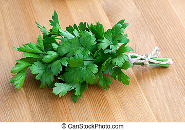 Green parsley lying on a wooden table.