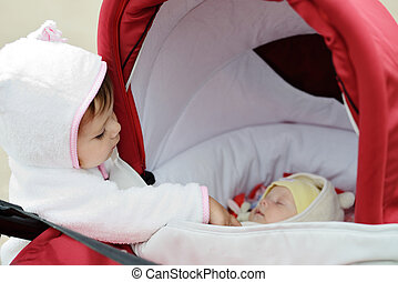 toddler and newborn - cunning toddler girl looking into the...