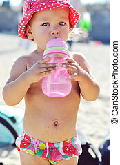 baby drinking water on the beach
