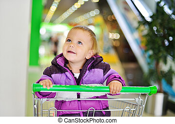 baby in shop - happy lovely baby sitting in shopping trolley