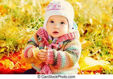 baby girl in fall park with leaf