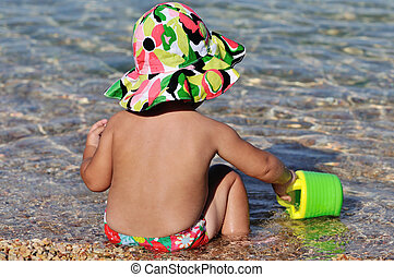 summer baby playing in the sea