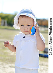 busy baby girl walking with toy phone