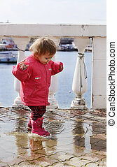 happy childhood of baby girl walking in puddle
