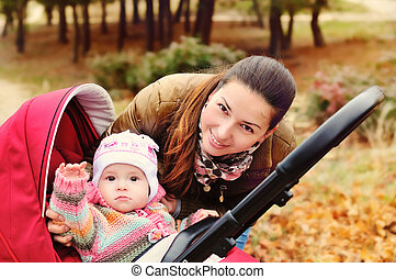 say hello - mother walking in the park with her baby in...