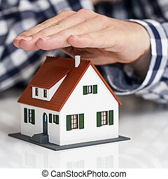 Hand over mini house with depth of field