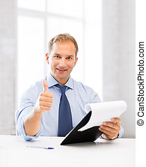 businessman with papers showing thumbs up - handsome...