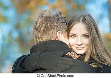 two young caucasian people embracing in the park