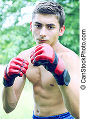Kickboxer in red gloves engaged on the nature