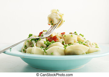 Boiled dumplings on a fork - Boiled dumplings with onion and...