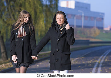 portrait of young caucasian couple walking together outdoor with