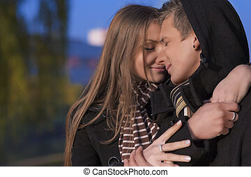 portrait of two beautiful caucasian people enjoying each other outside in park area