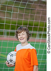 smiling young soccer player standing against goal with ball