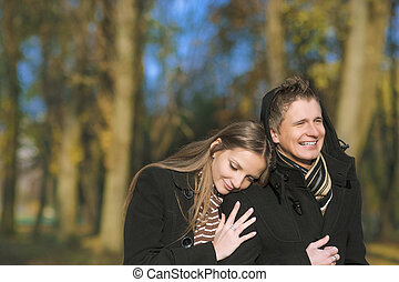 yuong caucasian couple walking in the park - portrait of two...