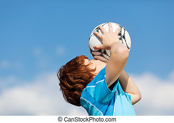 happy winner kissing soccer ball against blue sky