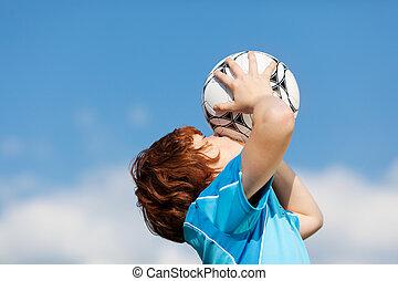 happy winner kissing soccer ball against blue sky