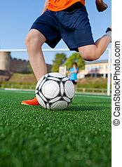 boy kicking soccer ball on field - low angle view of a boy...