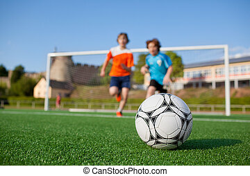 two young soccer players running to soccer ball - low angle...