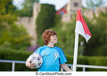 young boy standing at corner flag