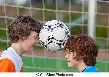 two friends balancing soccer ball between heads