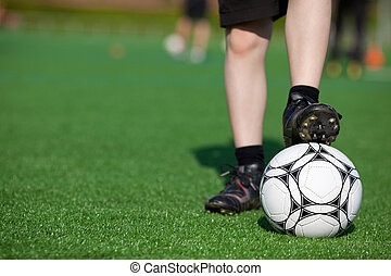 boy on soccer field waiting with soccer ball