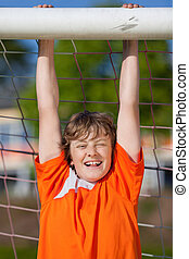 smiling young boy hanging on soccer goal and having fun