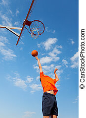 Boy Playing Basketball Against Blue Sky - Low angle view of...