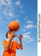 Basketball Player Spinning Ball Against Sky - Low angle view...