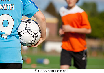 Boy Holding Soccer Ball With Friend Running In Background -...