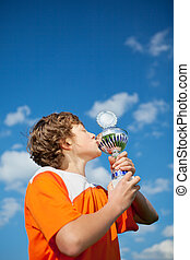 Little Boy Kissing Trophy Against Sky - Low angle view of...