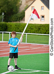 Boy With Soccer Ball Holding Flag While Standing At Corner