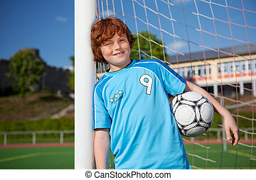 Boy Holding Soccer Ball While Leaning On Net Pole - Portrait...