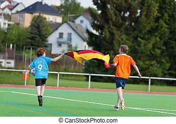 Boys Celebrating While Running With German Flag On Field -...