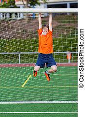 Boy Hanging On Net Pole At Soccer Field - Happy little boy...