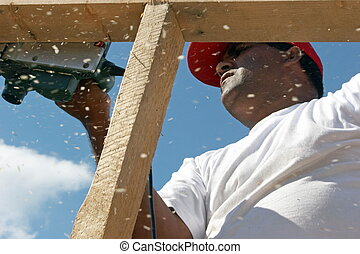 Worker on top - Worker polishing wood frame on top house
