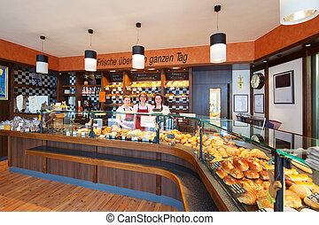 Friendly staff in a modern bakery - Interior view of a fully...