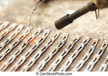 Cloceup jeweller at work silver soldering - Closeup jeweller...