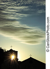 silhouette of a small church with the sun beams coming...