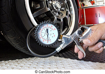 Checking air pressure in tire - Man checking air pressure in...