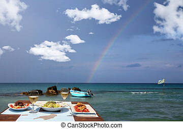 lunch table for two by the sea with nice rainbow