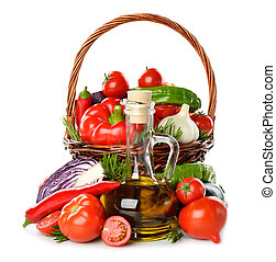 Vegetables in a basket and olive oil isolated on white...
