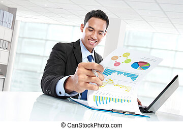successful businessman showing growth chart and smiling