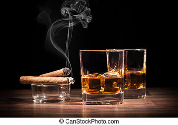 Whiskey drinks with smoking cigars on wooden table