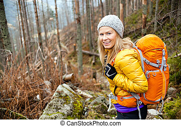 Woman hiking in autumn forest trail - Woman hiking in autumn...