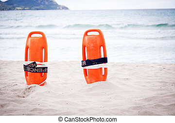 orange red life buoy in sand on beach at the sea object