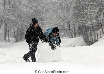 Snow fun - Girl and boy rolling a huge snowball