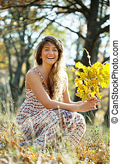 happy woman in autumn with oak posy - Outdoor portrait of...