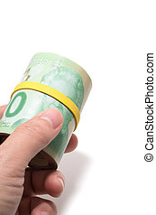 Hand holding a roll of 20 dollars Canadian with yellow...