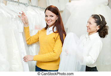 assistant  helps to girl  at shop of wedding fashion