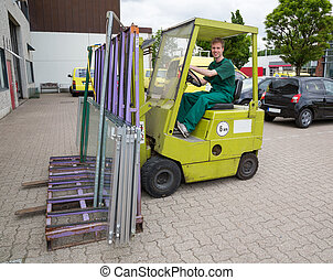 Glazier operating a forklift truck with panes of glass -...